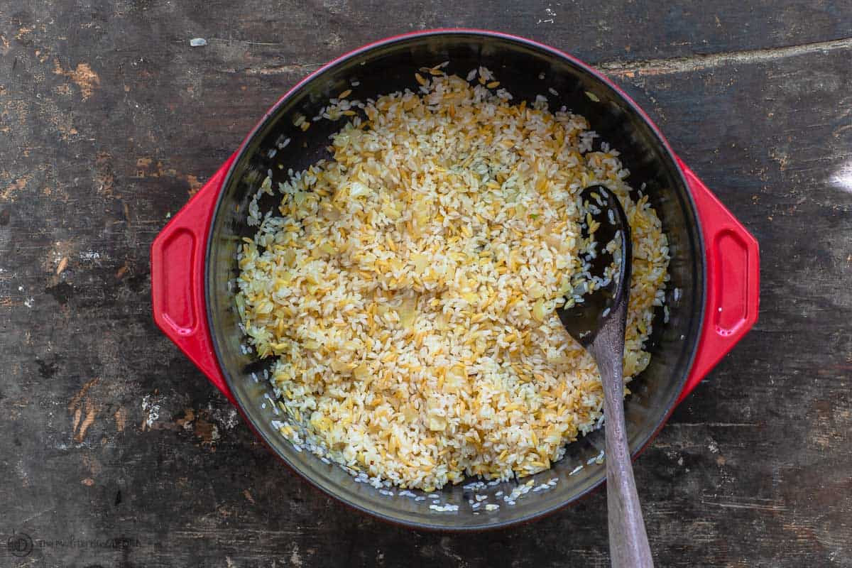 Orzo and rice are sauteed with onions, garlic and olive oil to start the Greek rice recipe