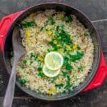 Greek lemon rice in pot cooking pot, garnished with fresh parsley, dill and lemon slices