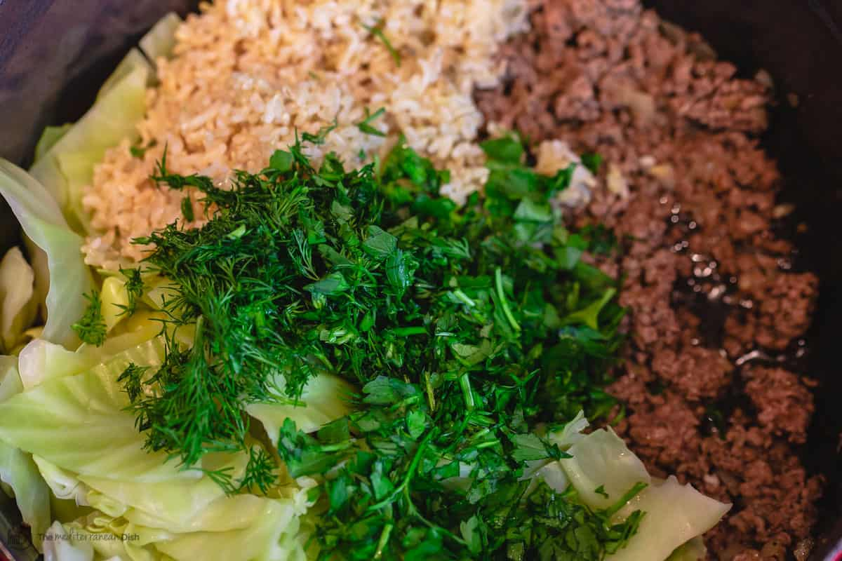 To make unstuffed cabbage rolls, a large pot with ground beef, cooked brown rice, cooked cabbage leaves, herbs and fresh herbs