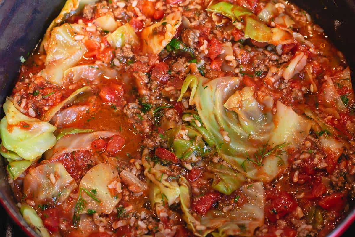 Diced tomato, tomato sauce and water are added to the large pot of unstuffed cabbage rolls ingredients