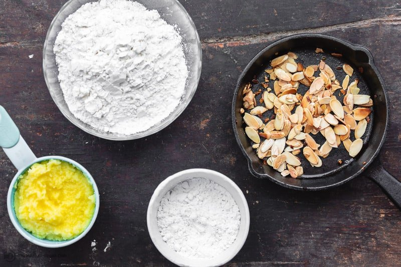 ingredients for butter cookies: ghee, powdered sugar, and flour. Toasted shaved almonds (optional)