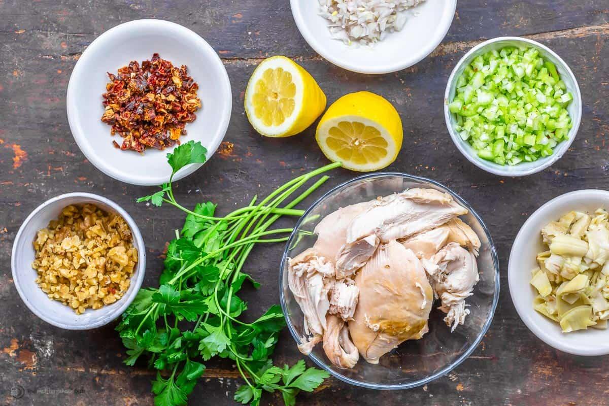 chicken salad ingredients including chicken, celery, lemon, walnuts, fresh herbs, sundried tomatoes