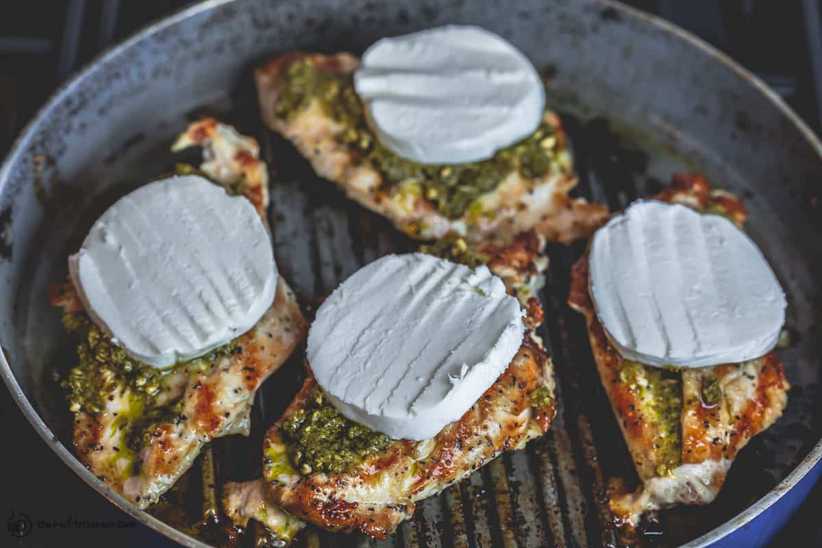 Grilled chicken breasts now topped with basil pesto and fresh mozzarella