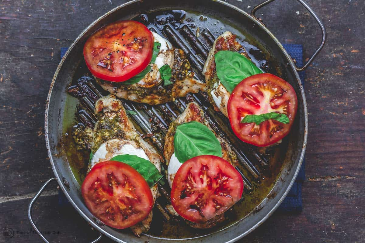 Finally, add fresh basil and tomato slices to complete caprese chicken
