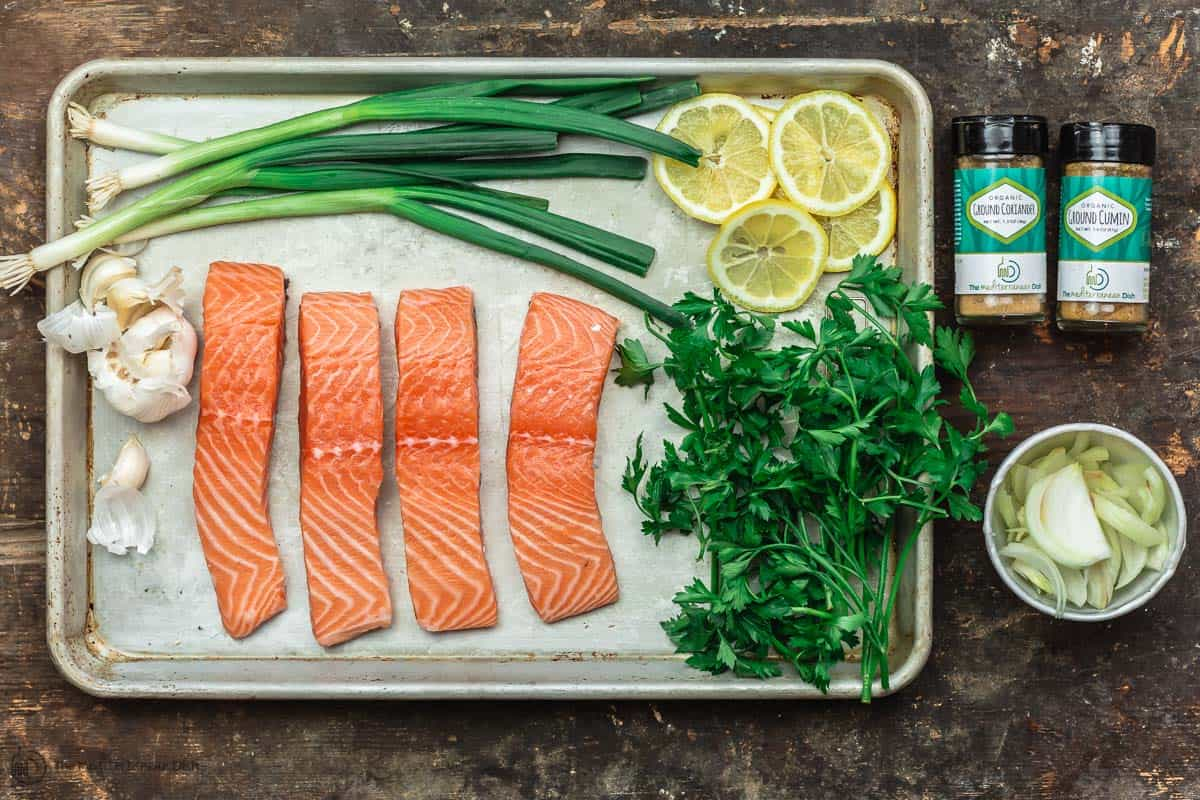 Steamed salmon ingredients. Salmon fillets, garlic, onions, fresh herbs and lemon