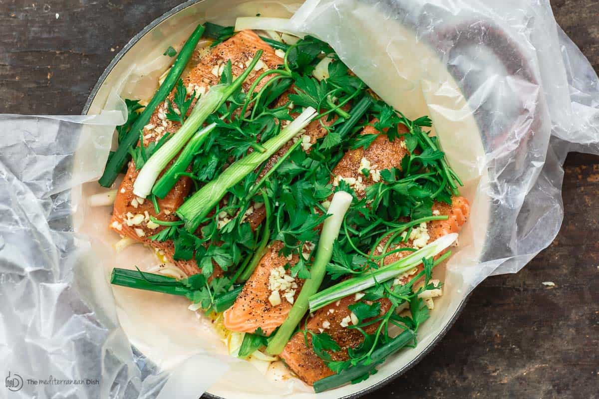 Uncooked salmon now topped with garlic, fresh parsley and green onions