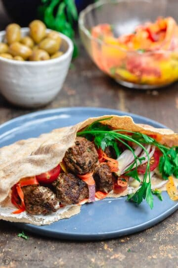 Moroccan Meatballs served in Pita Pockets with Fresh Vegetables and Carrot Salad. A side of Olives