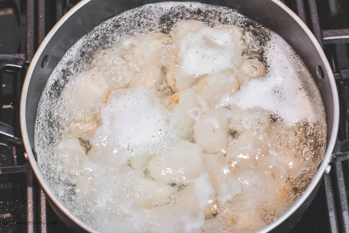 Potatoes are boiling in a pot of water