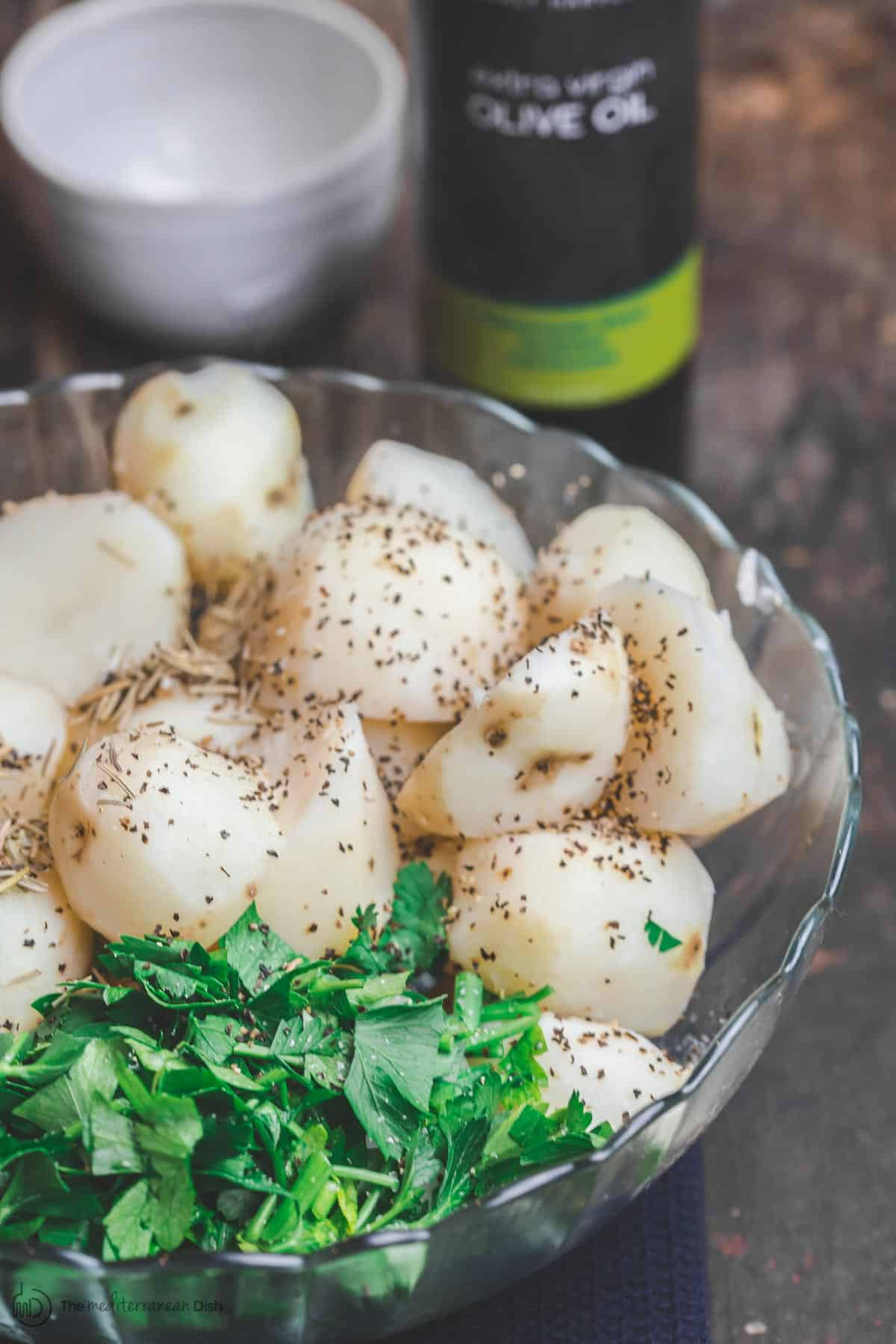 Boiled potatoes in a bowl with spices and fresh parsley. Olive oil ready for use