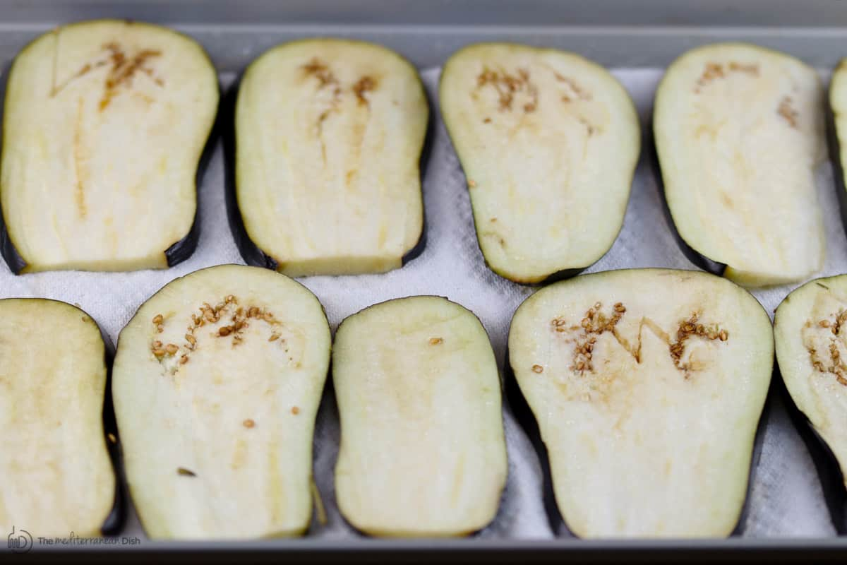 Slices of fresh eggplant laid on top of tray and salted