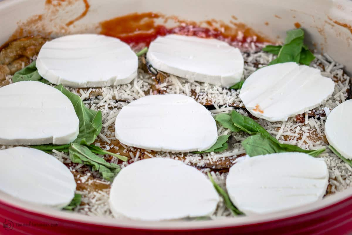 Another layer of mozzarella slices arranged on top of slices of eggplant, Parmesan, and fresh basil leaves
