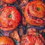 Greek stuffed tomatoes with rice and ground beef on a sheet pan