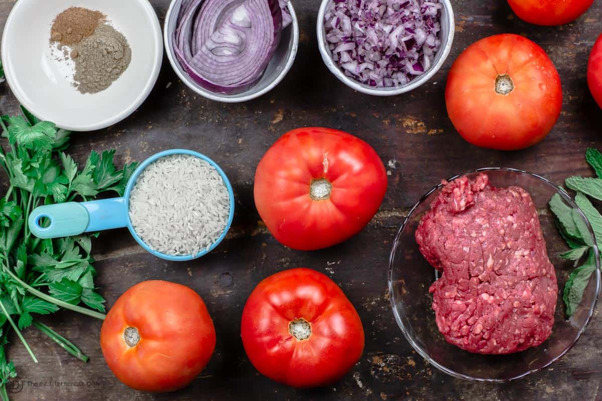 Ingredients for Greek stuffed tomatoes. Rice, beef, tomatoes, aromatics and herbs