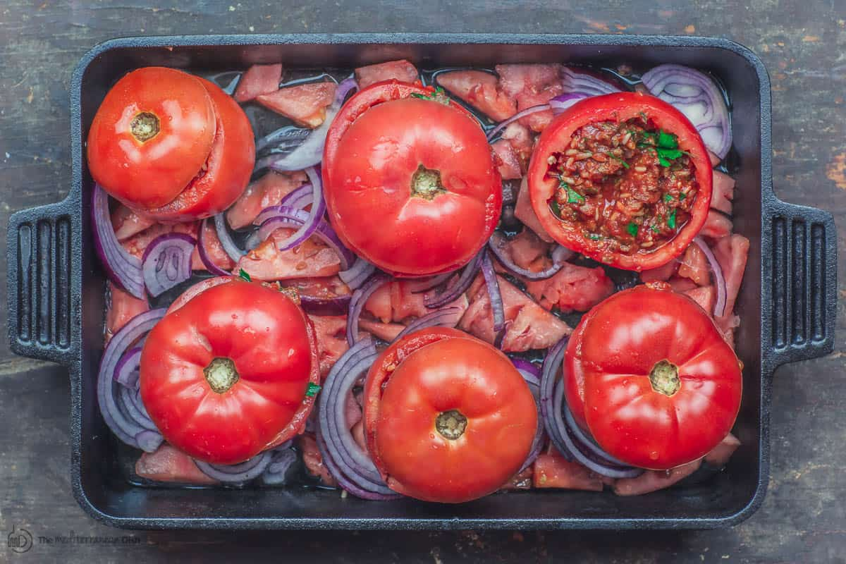Stuffed tomatoes in baking pan before cooking