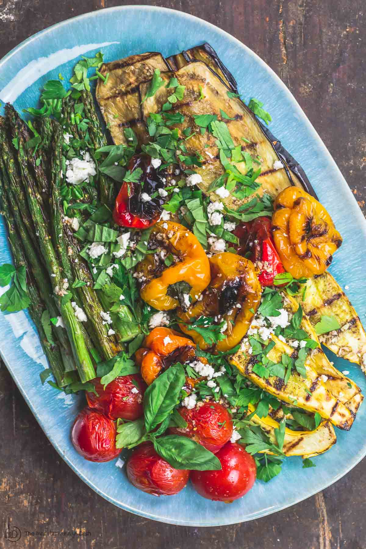 Grilled Vegetables Platter topped with Mediterranean dressing, fresh herbs and feta cheese