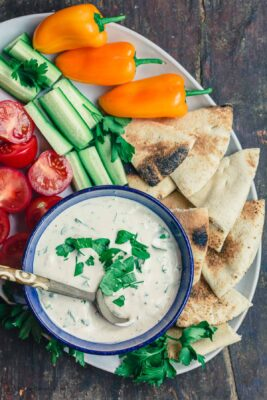 Tahini Sauce Platter with fresh vegetables and pita wedges