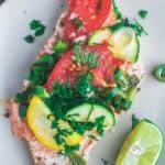 Oven baked salmon served on a plate with vegetables and parsley