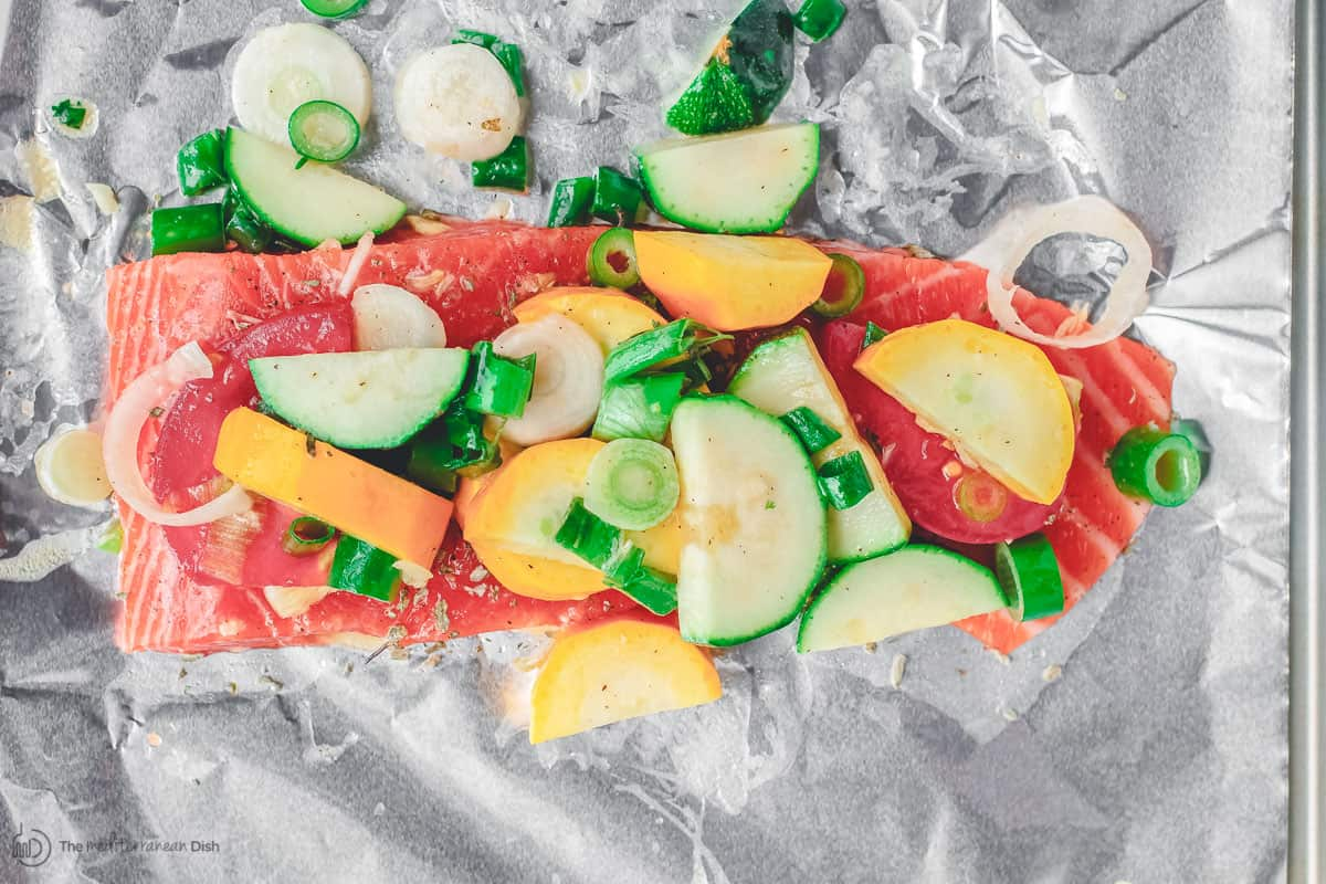 Sliced vegetables laid on top of salmon fillet in foil