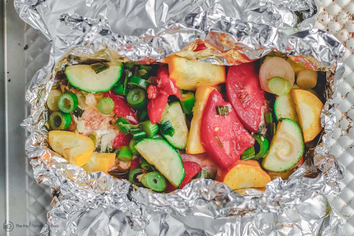 Salmon and vegetables individually wrapped in foil, open-faced