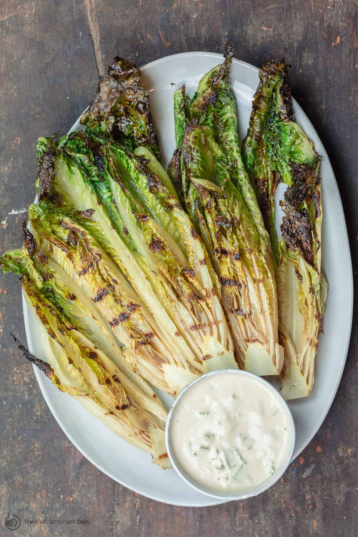 Grilled romaine lettuce with a side of tahini sauce
