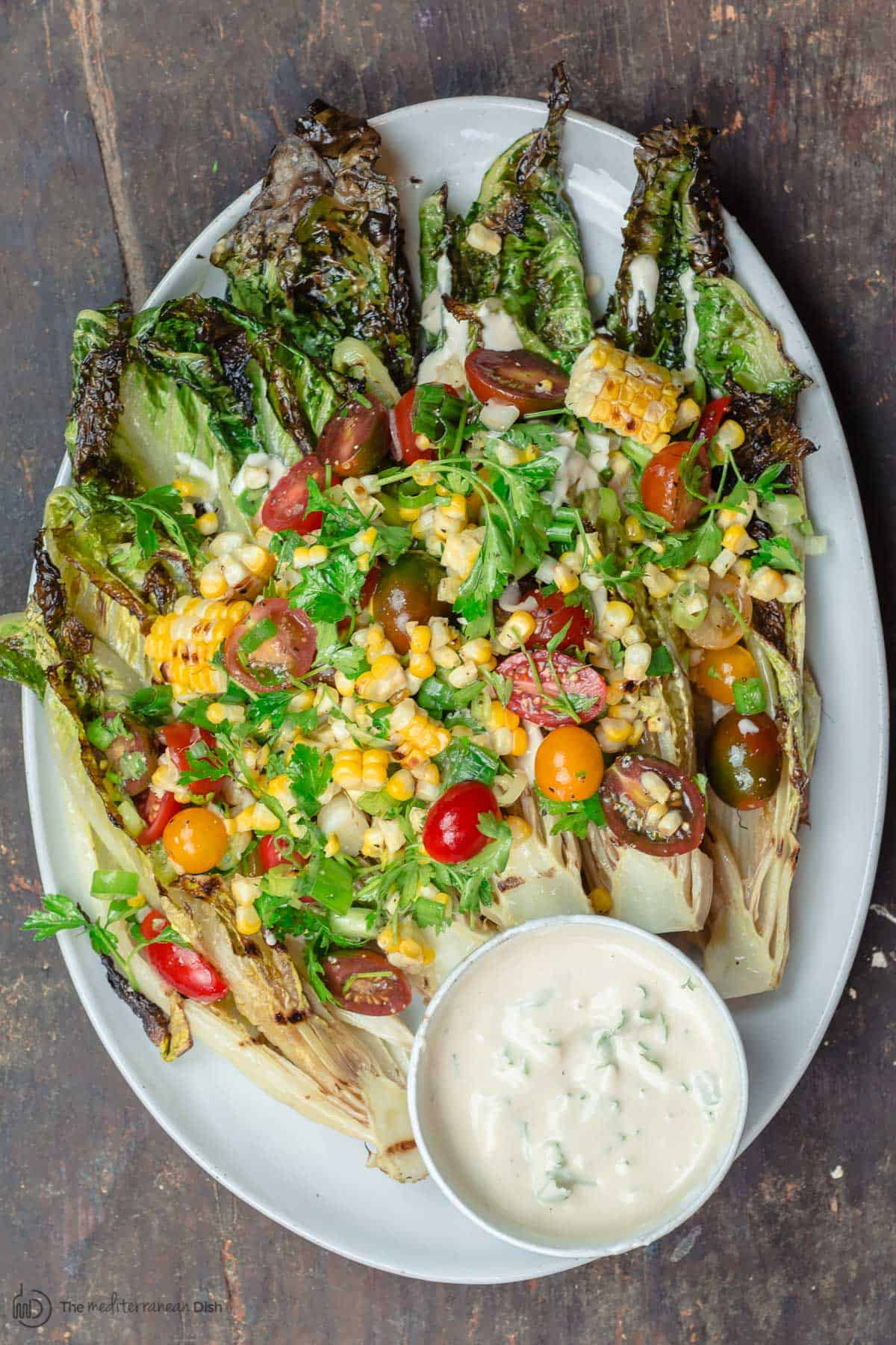 Grilled Lettuce Salad with corn, tomatoes, and a side of tahini sauce