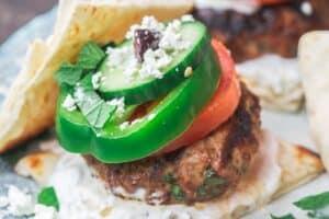 Greek lamb burgers with tzatziki sauce, vegetables, feta and olives