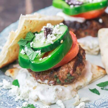 Greek lamb burgers with tzatziki sauce, vegetables, feta and olives