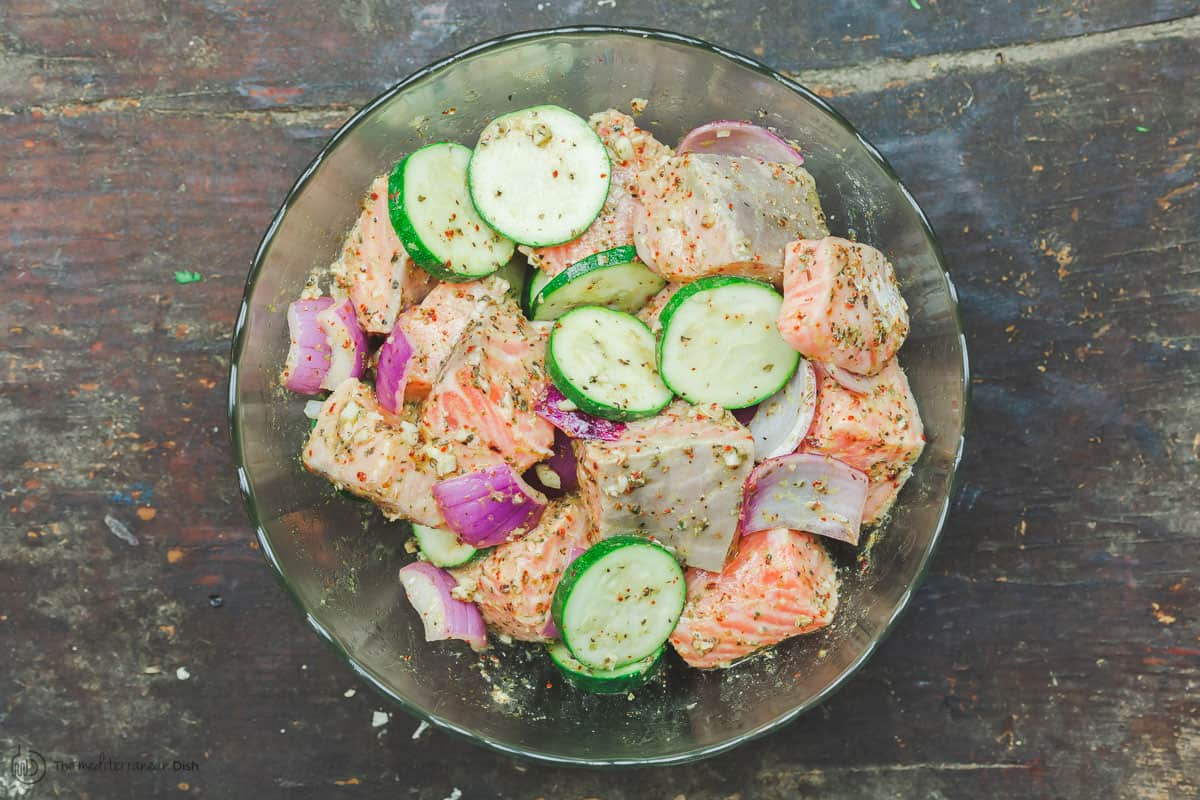 Salmon cutlets with slices of zucchini and red onion, marinated in a mixing bowl