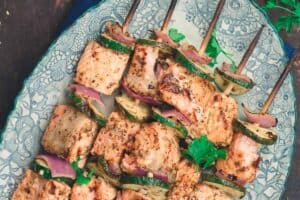 Mediterranean salmon kabobs served on a plate with tahini sauce