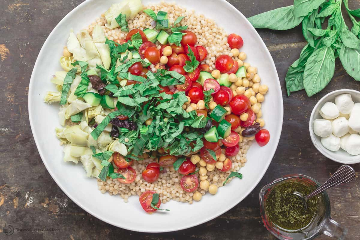 Ingredients for Mediterranean pearl couscous salad in a large mixing bowl