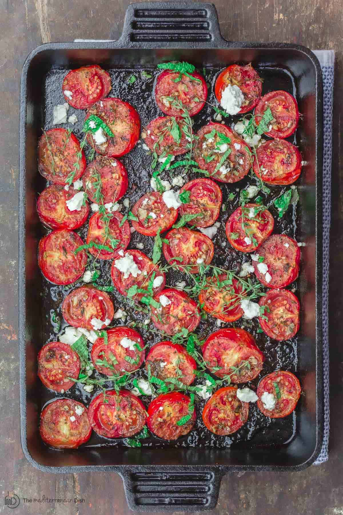 Oven roasted tomatoes with thyme and feta in a large cast iron pan