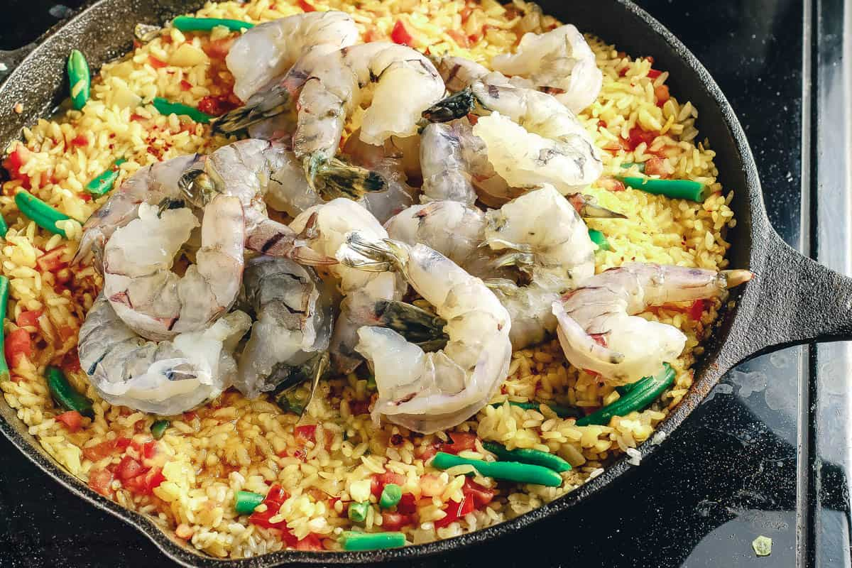 Paella in skillet with shrimp added