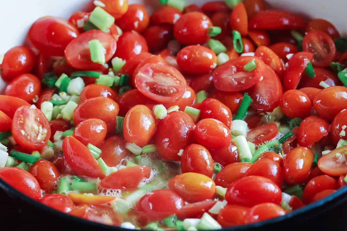 Roma tomatoes and diced green onions fried in a large pan