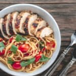 Chicken and spaghetti with tomatoes and basil served in a bowl