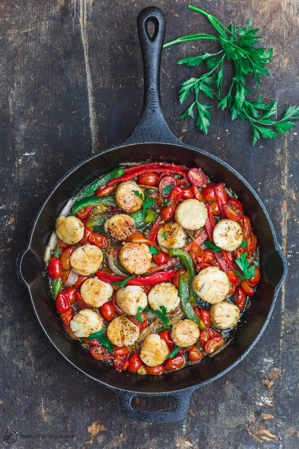 Scallops with tomatoes and bell peppers, sauteed in a cast iron skillet