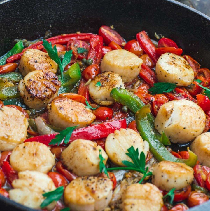 Scallops with vegetables in a cast iron skillet