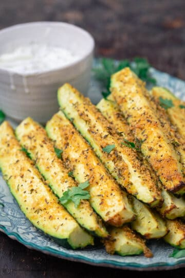 Baked zucchini sticks, stacked on a plate with a side of Tzatziki sauce