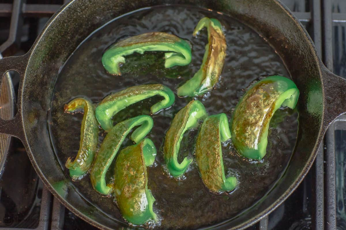 Green peppers fried in a cast iron pan