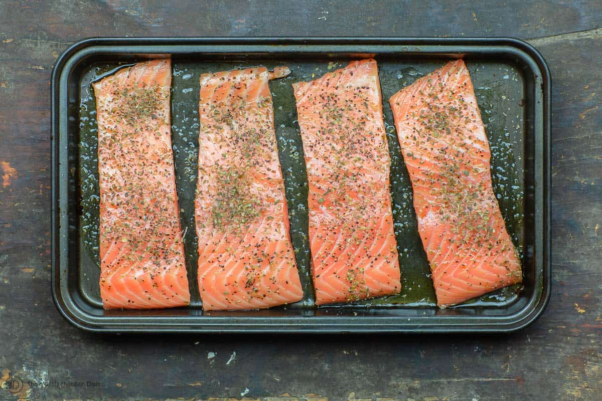 Uncooked salmon fillets seasoned in baking pan