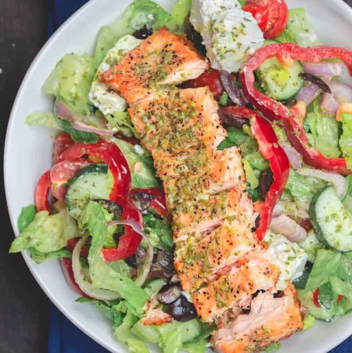 Salmon served on top of salad in a bowl
