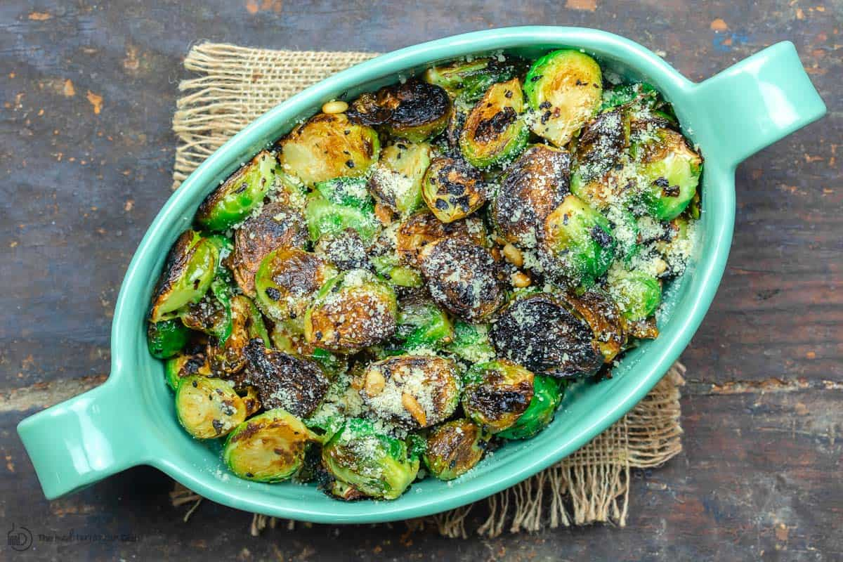 Fried brussels sprouts in serving dish with parmesan cheese and pine nuts