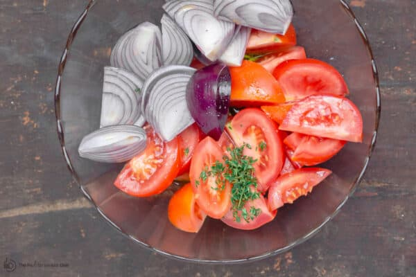 Tomatoes and onions quartered in a mixing bowl