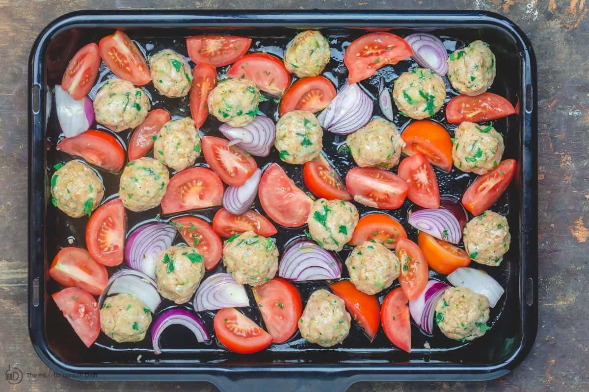 Chicken meatballs prepared in baking sheet with onions and tomatoes