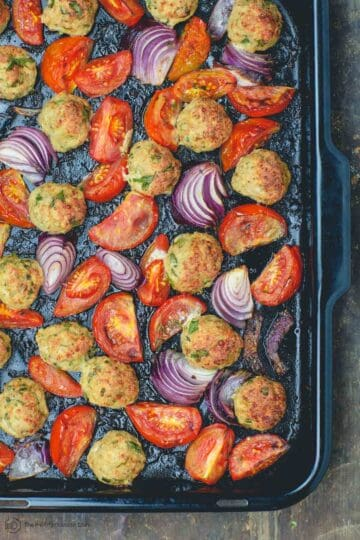 Italian baked chicken meatballs with onions and tomatoes in baking pan
