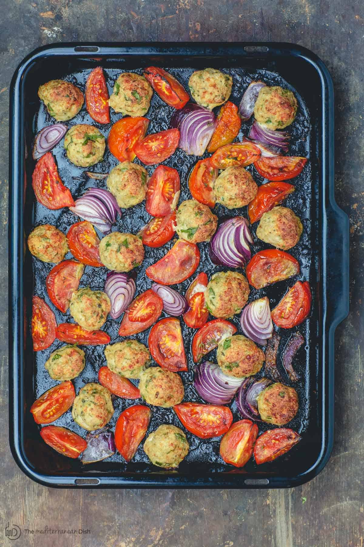 Baked chicken meatballs with onions and tomatoes in baking pan