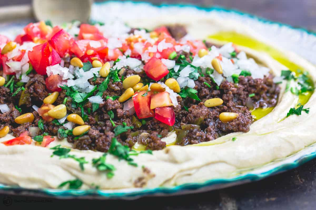 Hummus dip layered with ground beef, tomatoes, onions, parsley, and pine nuts
