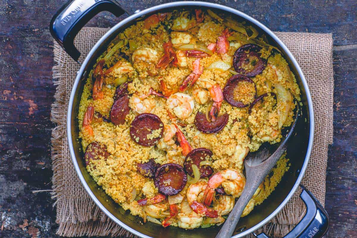 A large pot containing shrimp, spicy couscous and chorizo