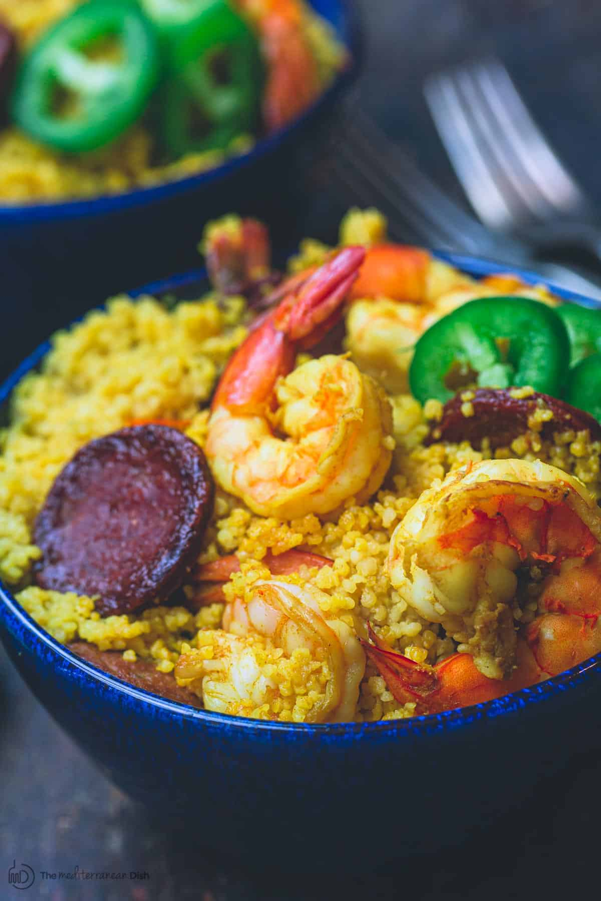 Spicy couscous with shrimp and chorizo in a bowl