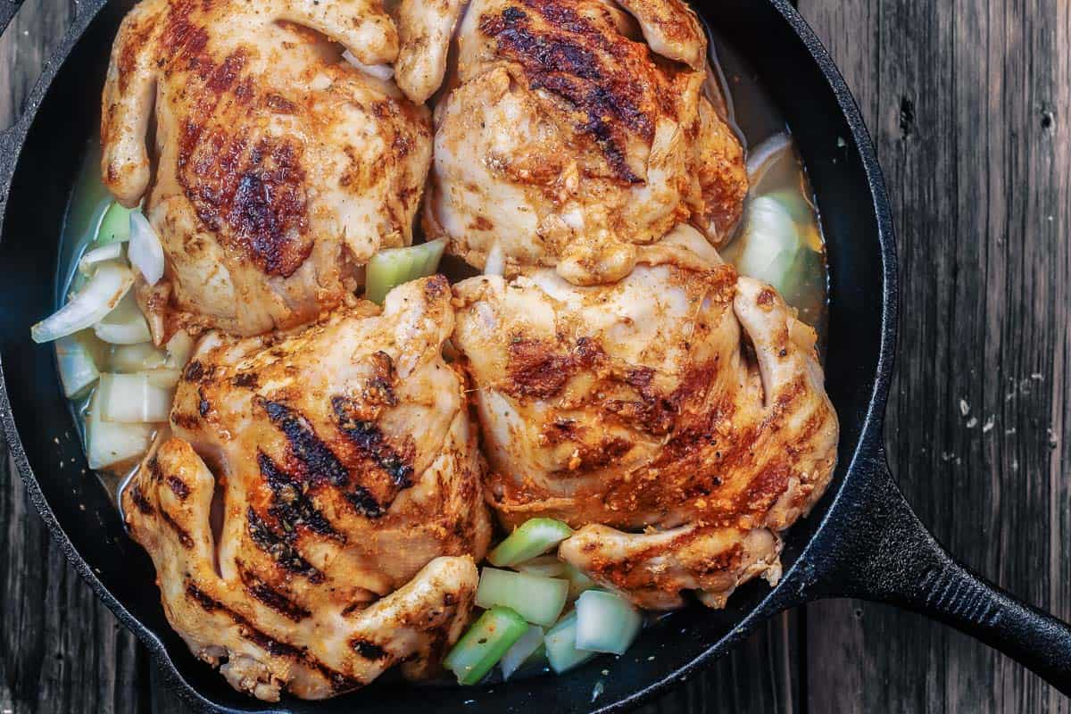 Cornish hen placed in cast iron skillet with onions and celery