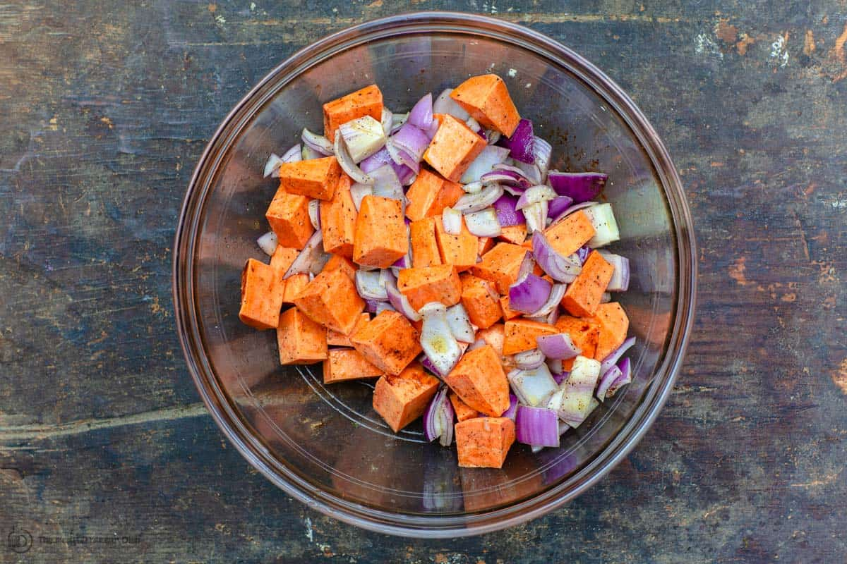 Freshly diced sweet potatoes and onions seasoned in mixing bowl